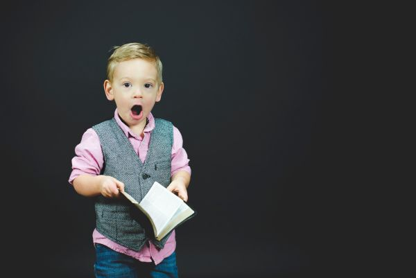 Young shocked boy holding open book