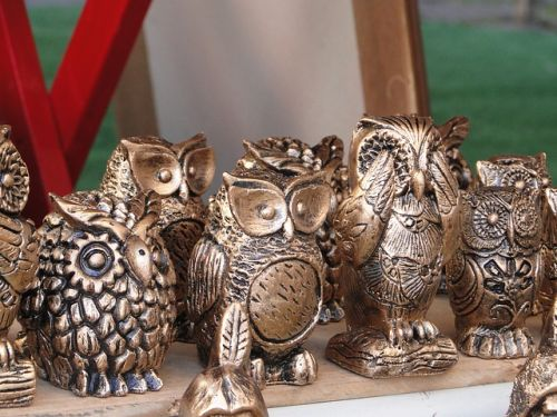 Metal owl ornaments huddled on a shelf