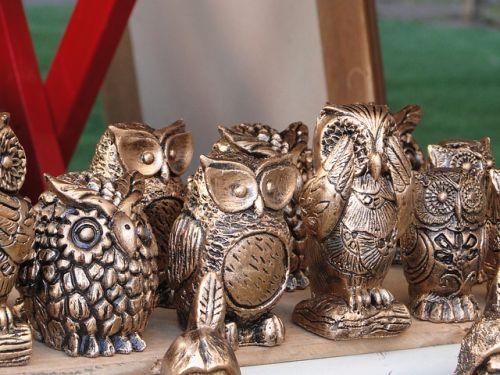 Metal owl ornaments huddled on a shelf