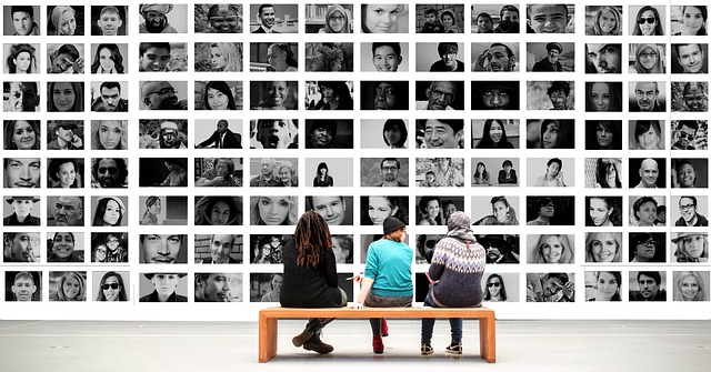Three people sat on bench in front of a wall of photo portraits