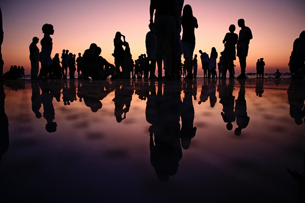 Silhouttes of people standing, their reflections on the floor