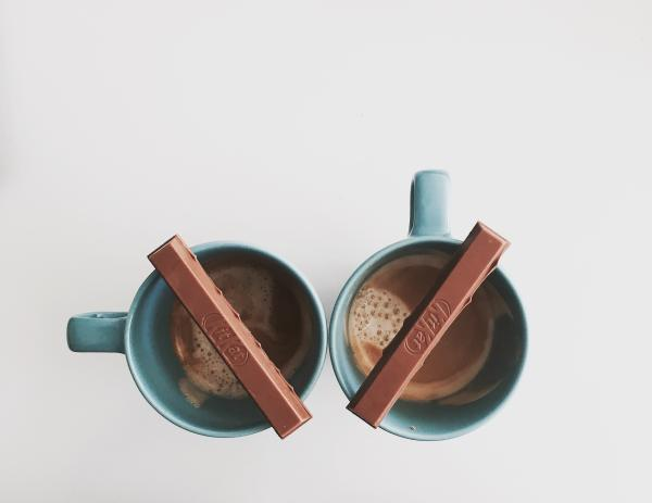 Two mugs of coffee with chocolate bars laying across the top