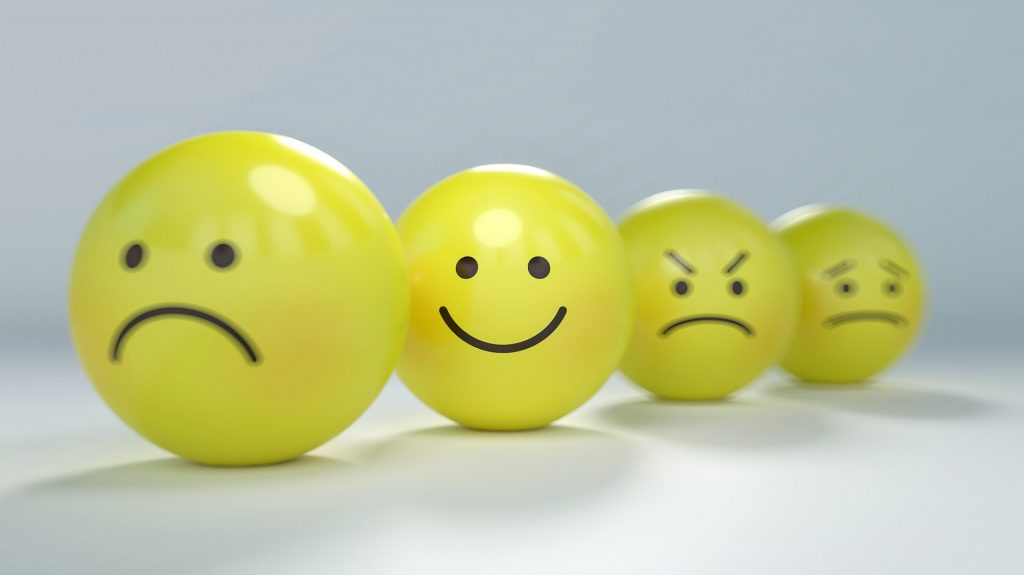 Four yellow balls with faces drawn in black ink: one sad, one happy, one angry and one uneasy