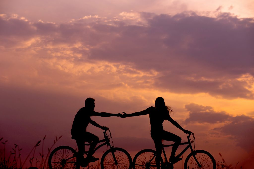 A woman on a bike reaching back to touch the hand of a man on a bike behind her