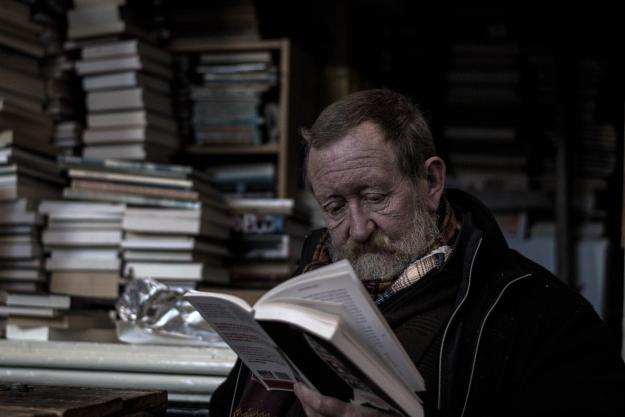Older man sat among piles of books, reading