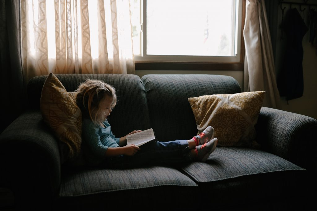 Young girl sat on a sofa, reading a book