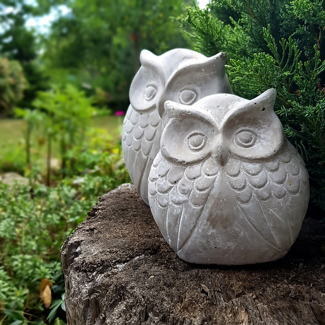 Two stone owl ornaments, on a log in front of a flourishing garden