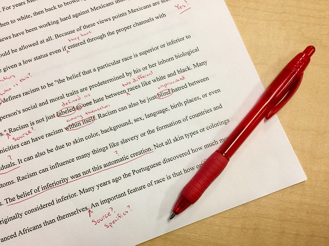 Page of printed text with editing mark-up in red pen